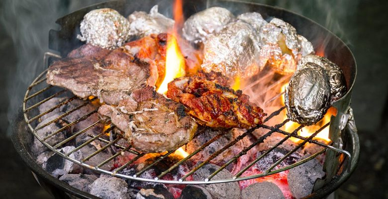 Tasty fresh appetizing meat beef on grill cooking on open fire on grill grid. Nature Background. Closeup.